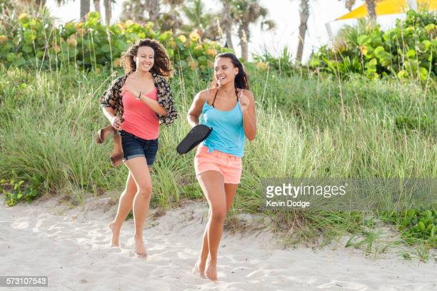 women carrying shoes running on beach - delray beach stock photos and pictures