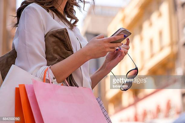 women carrying shoppings bags and using smartphone - shopping bag stock pictures, royalty-free photos & images