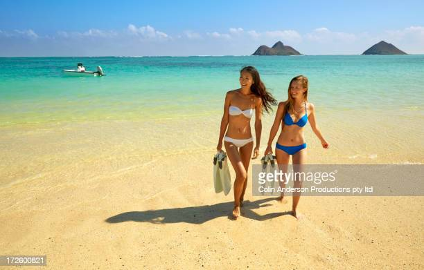Women carrying snorkel fins on beach