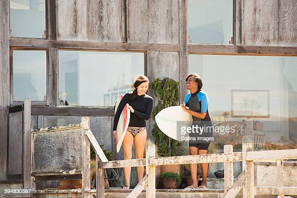 Women carrying surfboards on deck