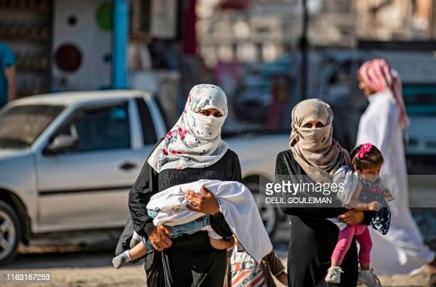 Women carrying their children walk in the northern Syrian city of Raqa, the former Syrian capital of the Islamic State group, on August 21, 2019. -...