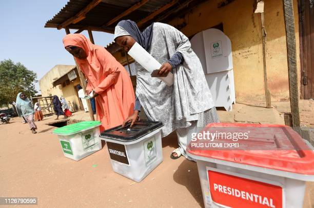 Women cast their ballots as they vote in the presidential and parliamentary elections on February 23 at a polling station in Daura Katsina State...