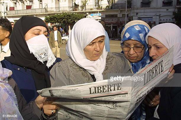 Women catch up with news as they read the independent Algerian daily 'Liberte' 11 January 2001 in Algiers before the start of a protest against...