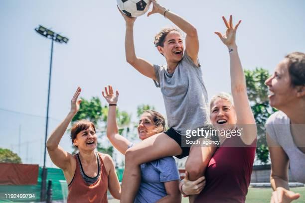 frauen feiern sieg auf einem fußballspielfeld - frauenfußball stock-fotos und bilder