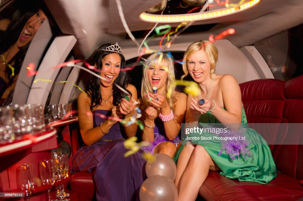 Women celebrating with confetti and balloons in limousine : Stock Photo