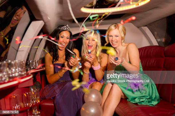 Women celebrating with confetti and balloons in limousine