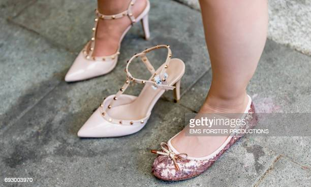women changes her rivet high heels pumps to much more comfortable sequin ballerina shoes because of a veins suffering and foot blows - varices fotografías e imágenes de stock