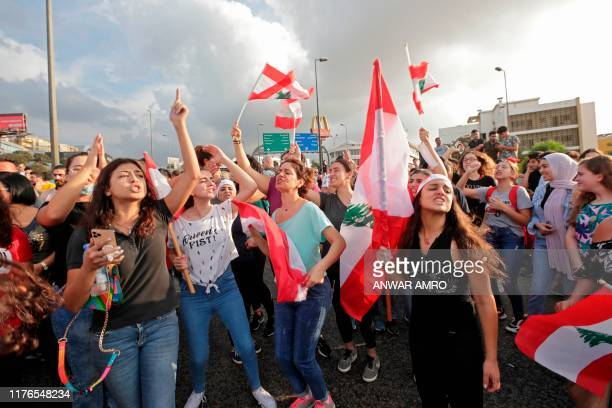 Women chant slogans and wave Lebanese national flags during a protest outside the presidential palace in Baabda east of the capital Beirut on October...