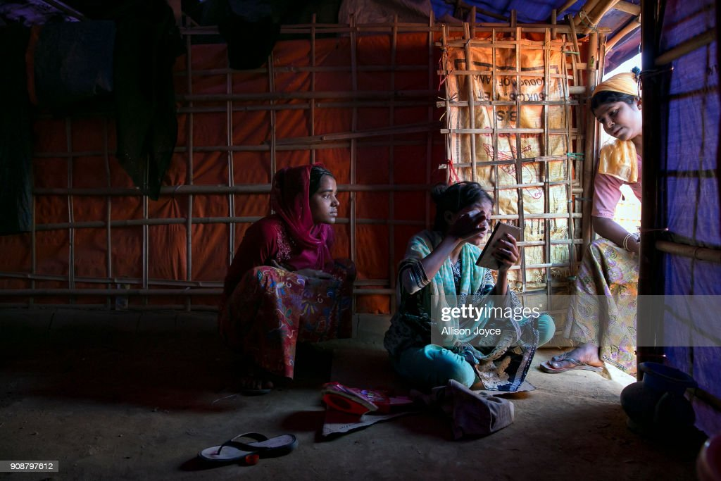 COX'S BAZAR, BANGLADESH - JANUARY 18: Women chat as they do their makeup on January 18, 2018 in Cox's Bazar, Bangladesh. In the refugee settlement of Balukhali, over 116 widows and orphans have found shelter within a dense settlement of 50 red tents where no men or boys over the age of 10 years old are allowed. More than 655,000 Muslim Rohingya have crossed the border into Bangladesh since August last year, when they fled Rakhine state after the Myanmar military launched a brutal crackdown which was described by the United Nations as 'ethnic cleansing'. Women and girls reportedly make about 51 percent of the distressed and traumatized Rohingya population in the refugee camps and face a high risk of being victims of human trafficking and sexual abuse, while adolescent girls aged between 13 and 20 risk getting involved in forced marriages. Many of the Rohingya women travelled alone after their husbands had been killed or taken away during the attacks on Rohingya villages as many continue to fear returning home due to the lack of security guarantees.
