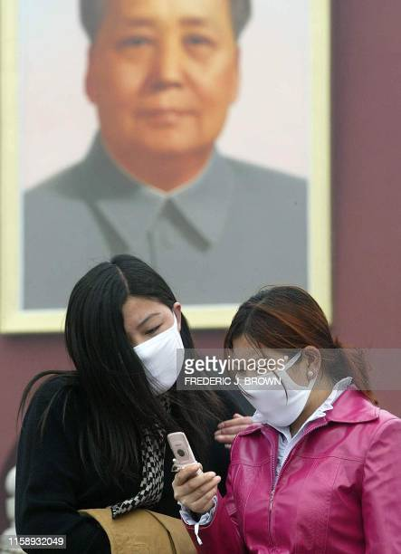 Women check messages on a mobile phone while wearing masks for prevention from SARS 22 April 2003 in front of the landmark Mao Zedong portrait...