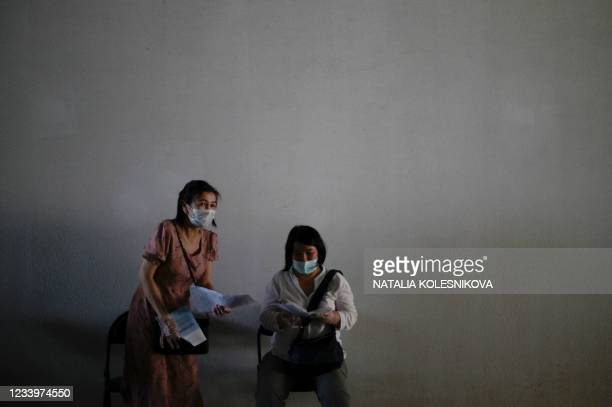 Women check their certificates after receiving a shot of Russia's Sputnik Lite Covid-19 vaccine at a vaccination point for foreign people at the...