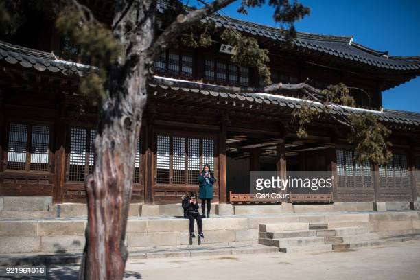 Women check their phones as they visit Deoksugung Palace on February 21 2018 in Seoul South Korea With tourists visiting from around the world...