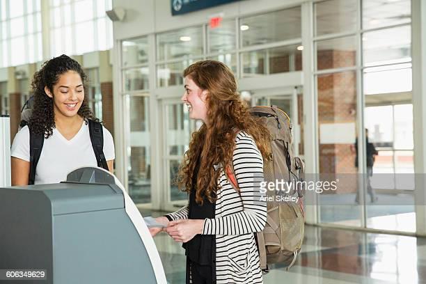 Women checking in at airport kiosk