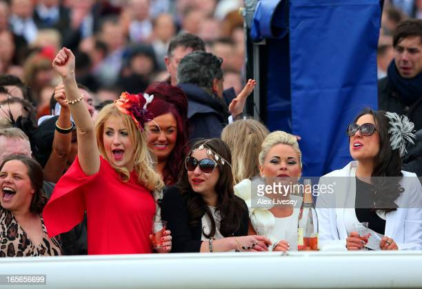 Women cheer on the horses during the Rose Appeal Supports Alder Hey Top Novices' Hurdle on Ladies Day at Aintree Racecourse on April 5 2013 in...