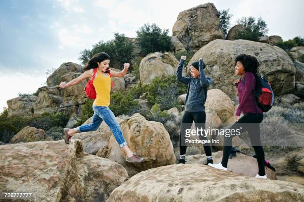 Women cheering friend jumping on rock formation