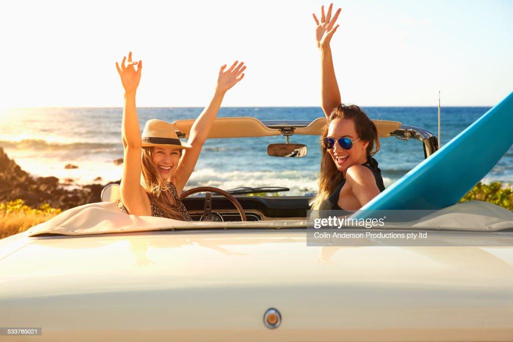 Women cheering in convertible on beach : Stock Photo