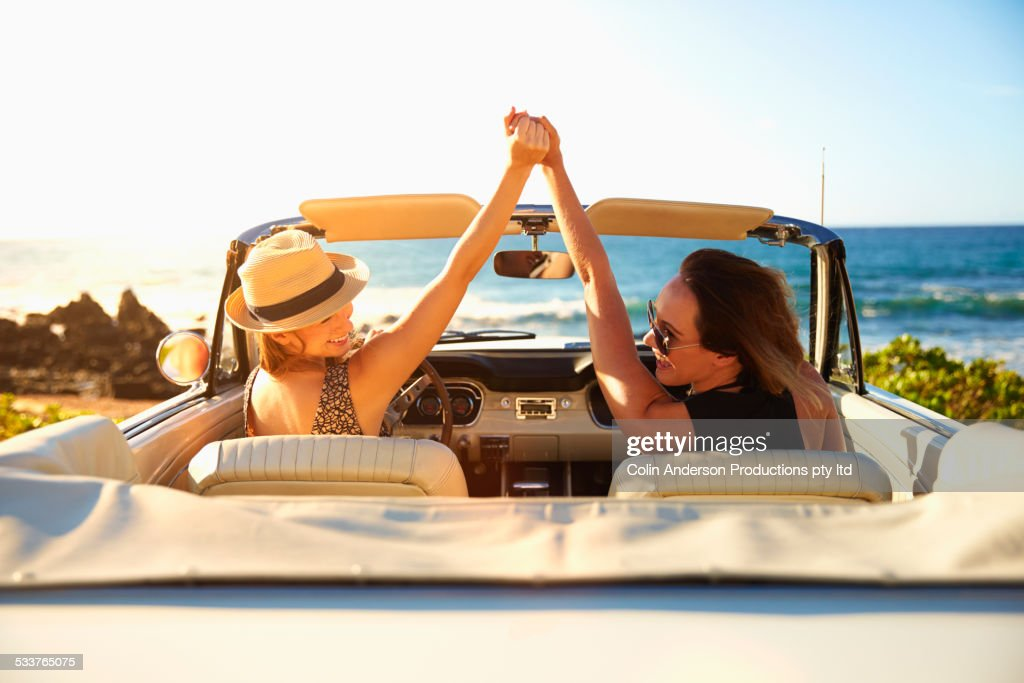 Women cheering in convertible on beach : Foto stock