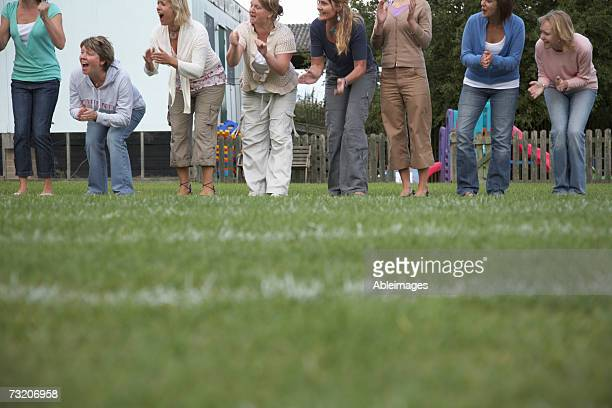 Women cheering on sidelines of football field