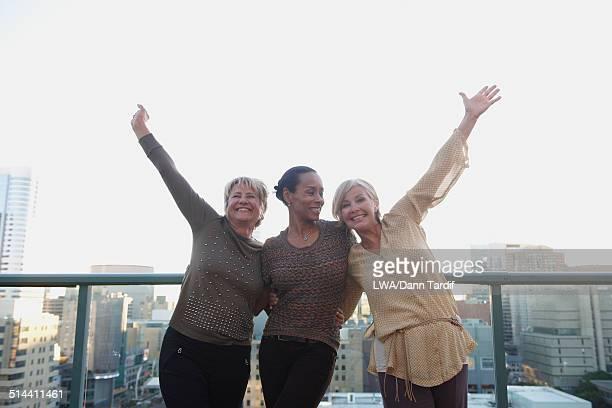 Women cheering on urban rooftop