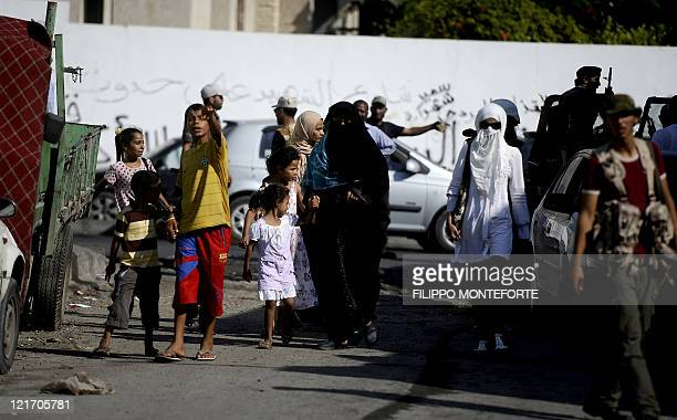 Women children and rebel fighters gather on a street in the Libyan capital Tripoli on August 22 as heavy fighting raged near the Tripoli compound of...