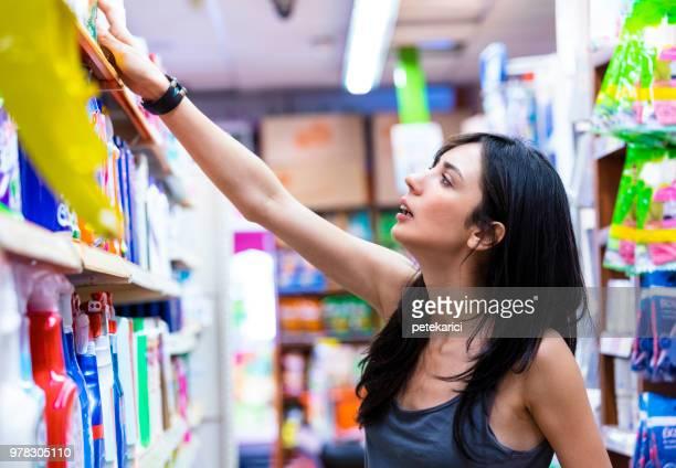 La mujer elige productos de limpieza de casa