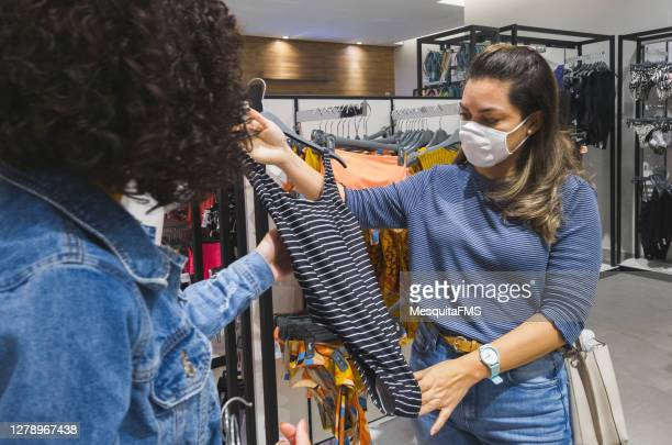 women choosing clothes in shopping mall - swimwear stock pictures, royalty-free photos & images