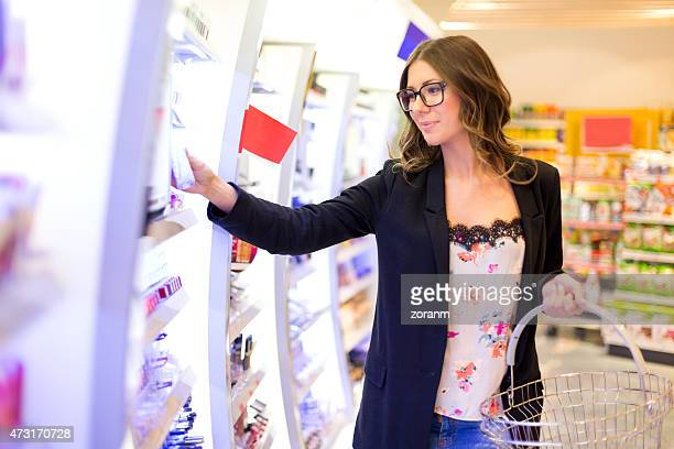 Women choosing lipgloss in shopping mall