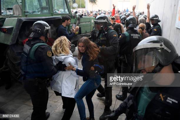 Women clash with Spanish Guardia Civil guards outside a polling station in Sant Julia de Ramis where Catalan president is supposed to vote on October...