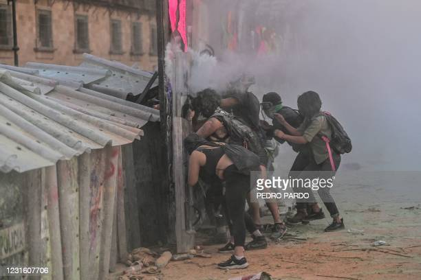 Women clash with the police, behind a fence in front of the National Palace, as they protest during a demonstration to commemorate the International...