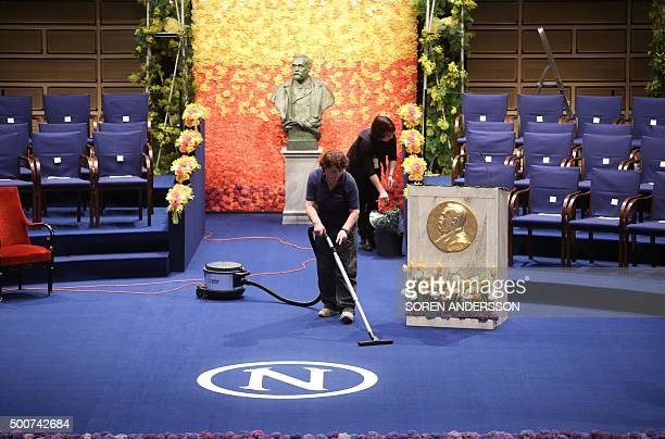 Women clean the carpet in front of a bust of Swedish philanthropist and scientist Alfred Nobel at the Stockholm Concert Hall as preparations are...