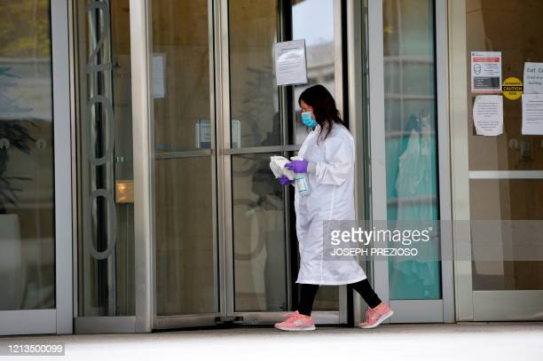 A women cleans the entrance doors to Moderna headquarters in Cambridge Massachusetts on May 18 2020 US biotech firm Moderna reported promising early...