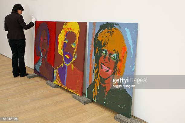 A women cleans the frame of an artwork by Andy Warhol at the museum Brandhorst on May 15 2009 in Munich The museum which shows works from the...