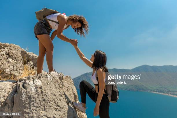 women climbing rock wall together - doing a favor stock pictures, royalty-free photos & images