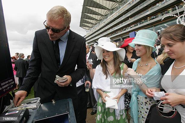Women collect their race winnings from a bookie during Ladies Day on day three of Royal Ascot on June 21 2007 in Ascot Berkshire England