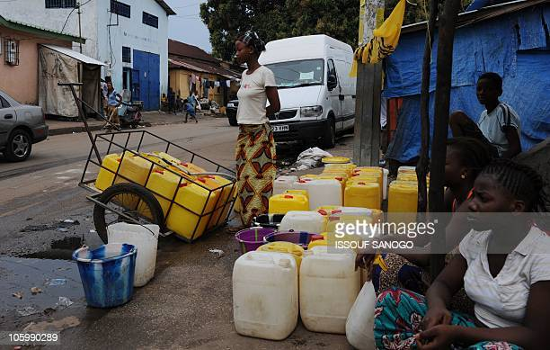 Women collect water on the streets of Conakry on Octobre 24 2010 The two candidates in Guinea's presidential election appealed for calm yesterday...