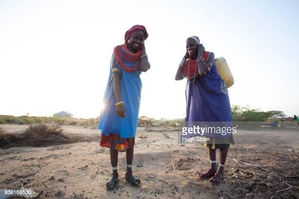 Women collecting clean water from borehole in desert. Samburu. Kenya.