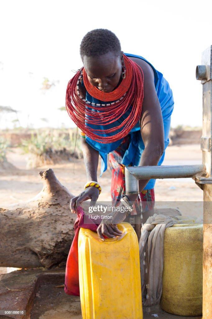 Women collecting clean water from borehole in desert. Samburu. Kenya. : ストックフォト