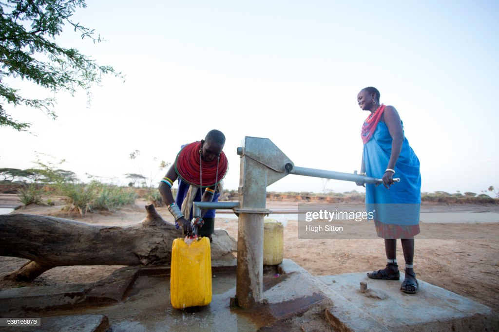Women collecting clean water from borehole in desert. Samburu. Kenya. : Stock Photo