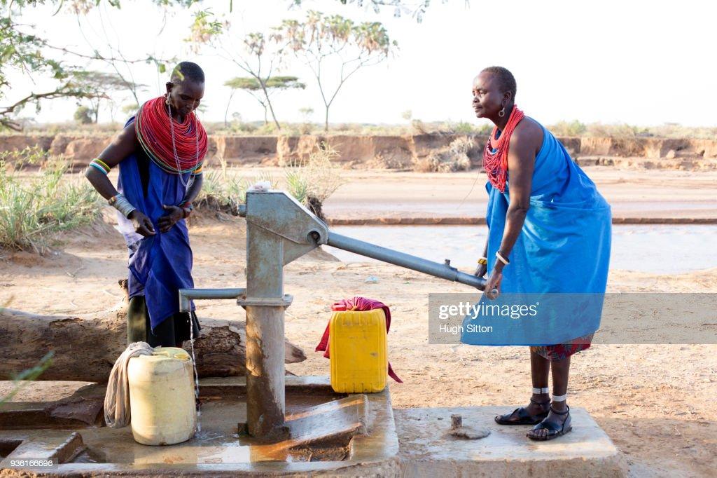 Women collecting clean water from borehole in desert. Samburu. Kenya. : Stock Photo