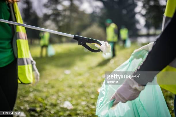 vrouwen verzamelen onzin met afval kiezer - plukken stockfoto's en -beelden