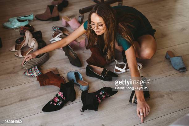 women collecting shoes while sitting on hardwood floor at home - collection photos et images de collection