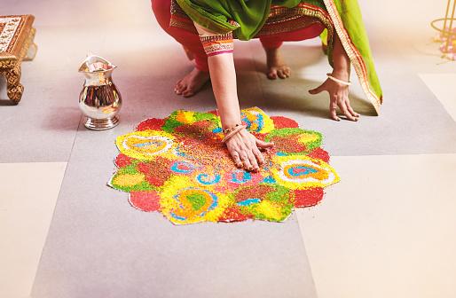 Women coloring traditional rice art (Rangoli) for indian marriage rituals 972734372