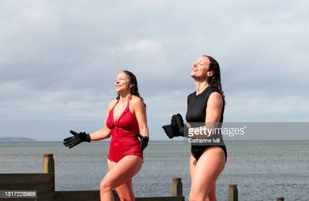 women come out of the water after open water swimming - female friendship stock pictures, royalty-free photos & images