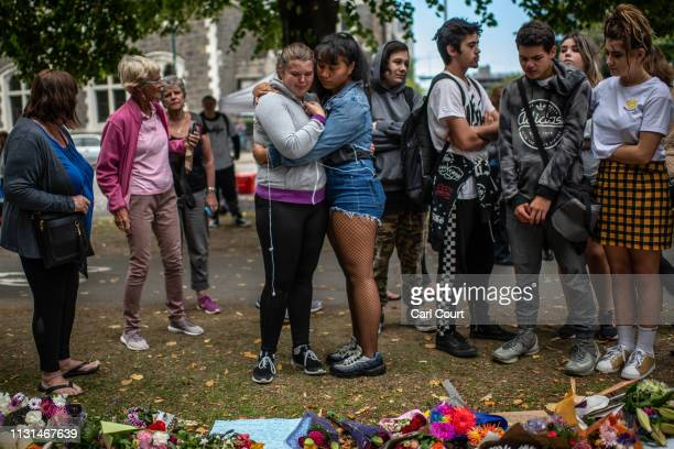 Women comfort each other as they view flowers and tributes by the botanical gardens on March 19, 2019 in Christchurch, New Zealand. 50 people were...