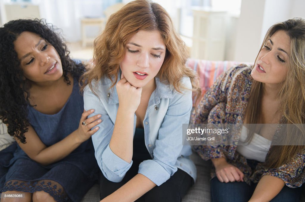 Women comforting sad friend on sofa in living room : Stock Photo