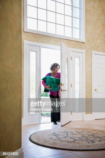 Women Coming Through Front Door Holding Groceries High Res