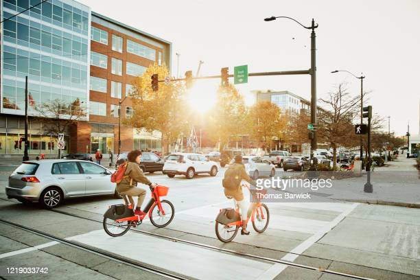 women commuting on electric bike share bikes during rush hour - sharing economy stock pictures, royalty-free photos & images