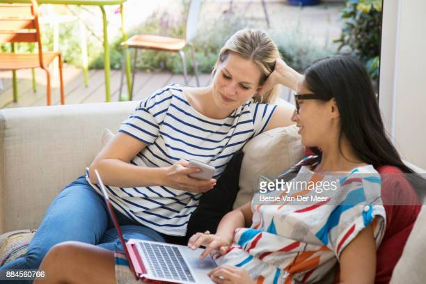 Women comparing information on digital devices, sitting on sofa.