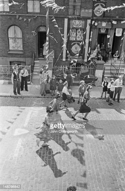 Women competing in an eggandspoon race held at a party to celebrate the coronation of Queen Elizabeth II held in Morpeth Street in London's East End...