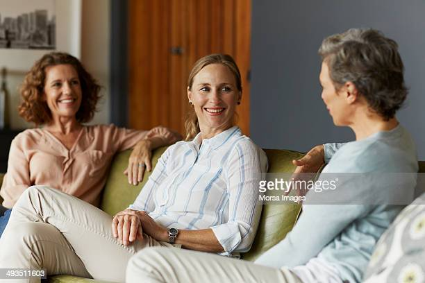 women conversing in living room - grupo pequeño de personas fotografías e imágenes de stock